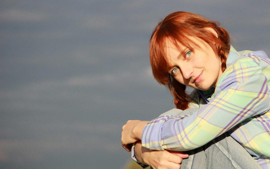 Лолита Быстрова сидит обняв колени на фоне неба