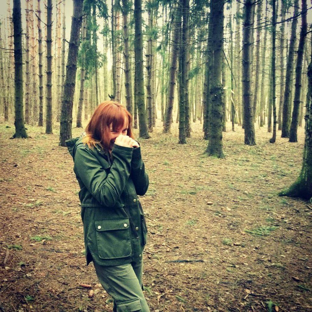 Лолита Быстрова в зеленой куртке в лесопарке