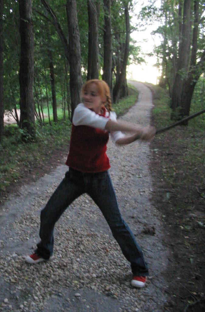 Лолита Быстрова размахивает палкой в лесу