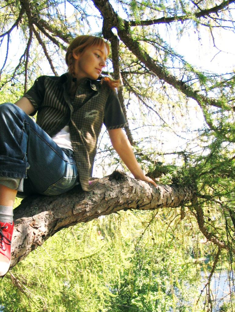 Лолита Быстрова сидит на ветке дерева