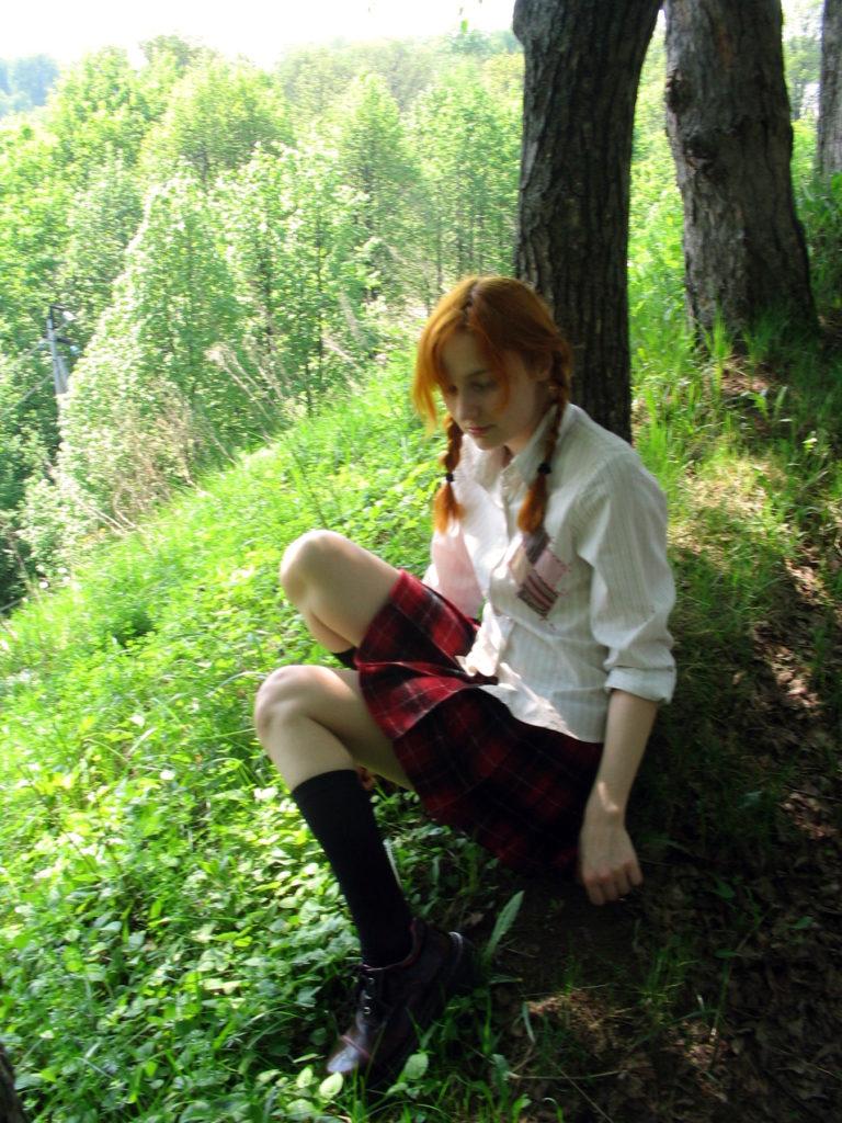 Лолита Быстрова в шотландке и гольфах сидит под деревом