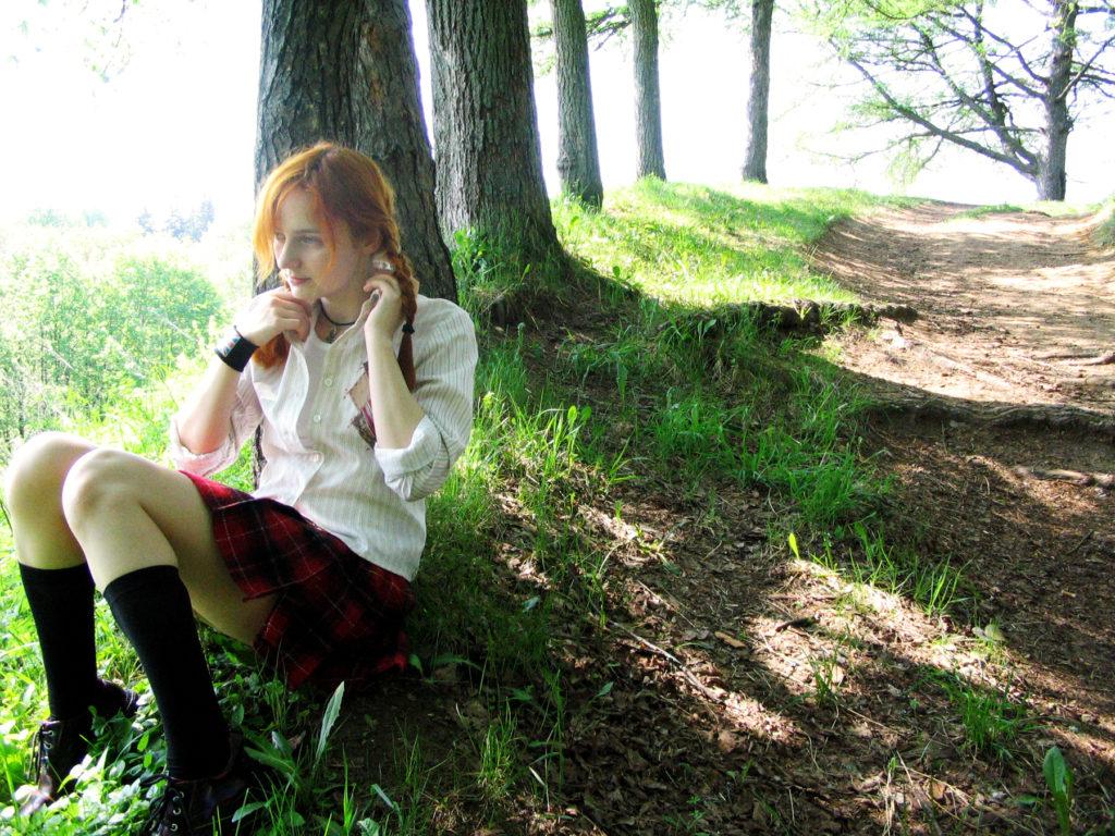 Лолита Быстрова в школьной форме сидит под деревом