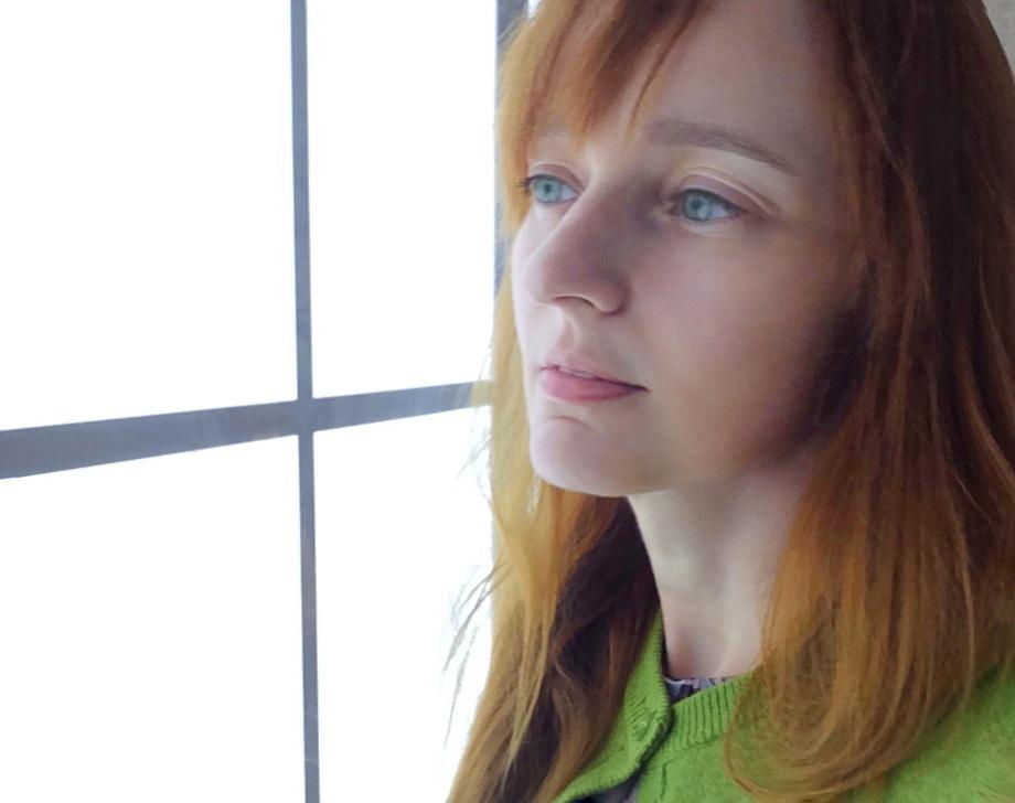 Лолита Быстрова в зеленом кардигане у окна