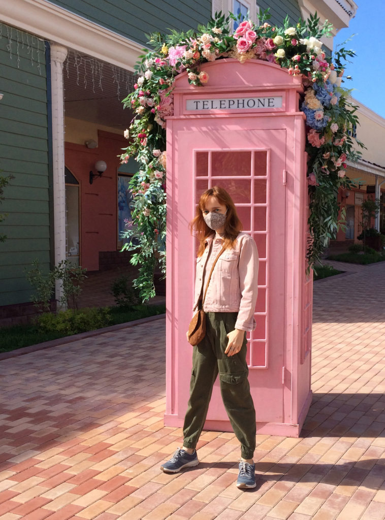 Лолита Быстрова в маске возле розовой телефонной будки