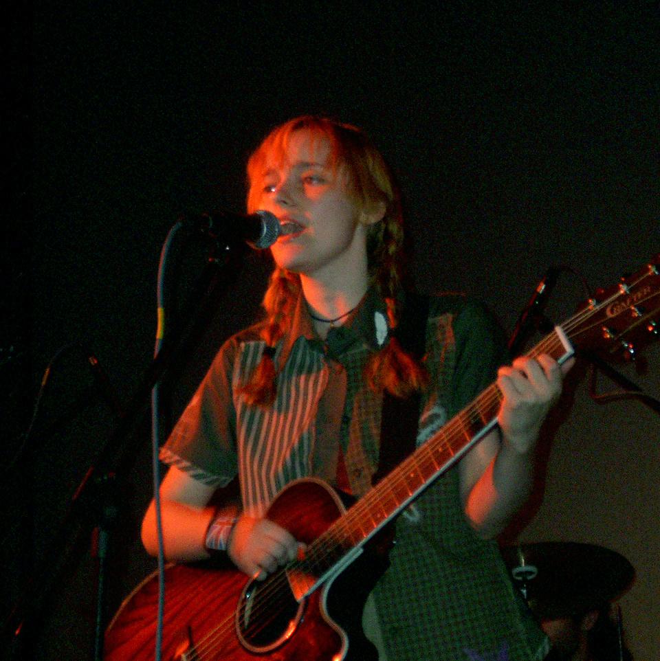 Лолита Быстрова поет с гитарой в руках