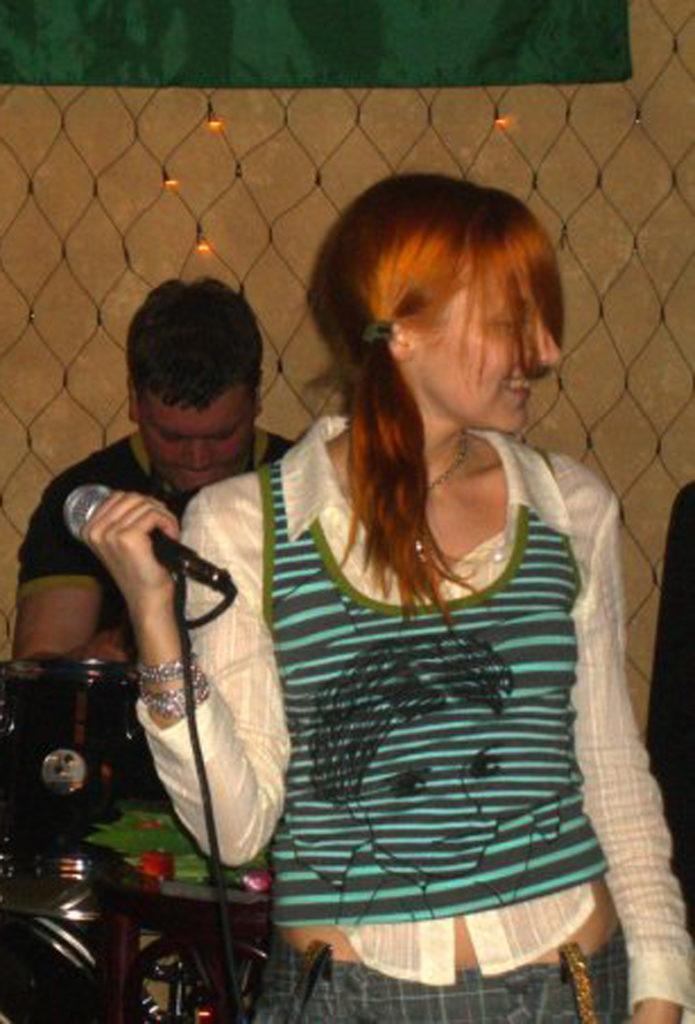 Лолита Быстрова с микрофоном и в зеленой полосатой майке